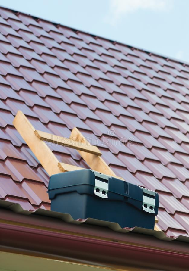 A caixa das ferramentas está no telhado da casa foto de stock royalty free