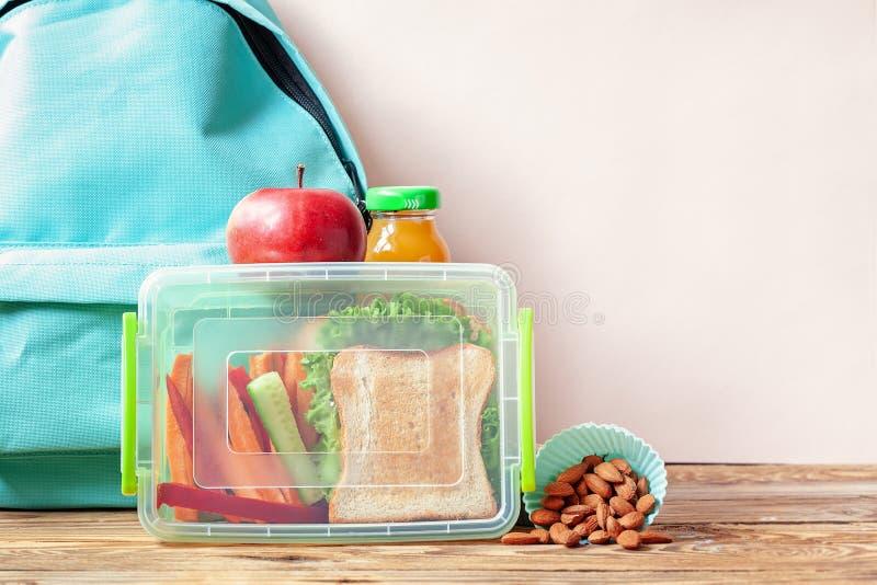 Caixa de almoço escolar com sanduíche, vegetais, suco e amêndoas na tabela imagens de stock