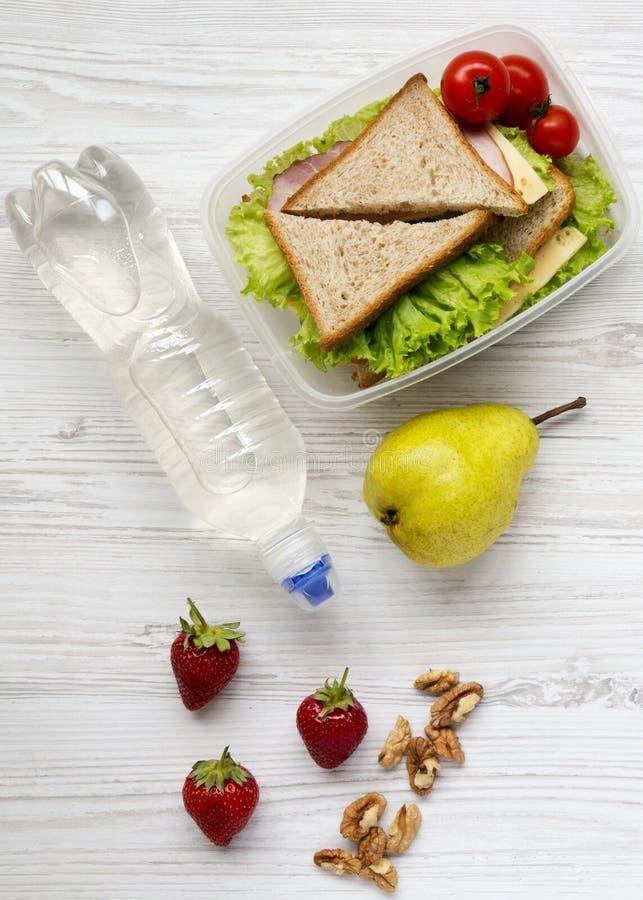 Caixa de almoço escolar saudável com os sanduíches orgânicos frescos, as nozes, a garrafa da água e os frutos dos vegetais em uma imagem de stock royalty free