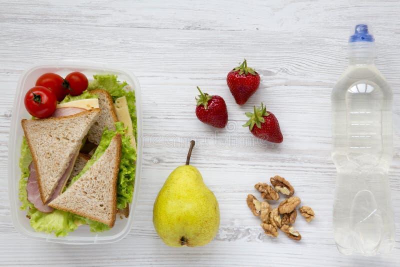Caixa de almoço escolar saudável com os sanduíches orgânicos frescos, as nozes, a garrafa da água e os frutos dos vegetais no fun fotos de stock