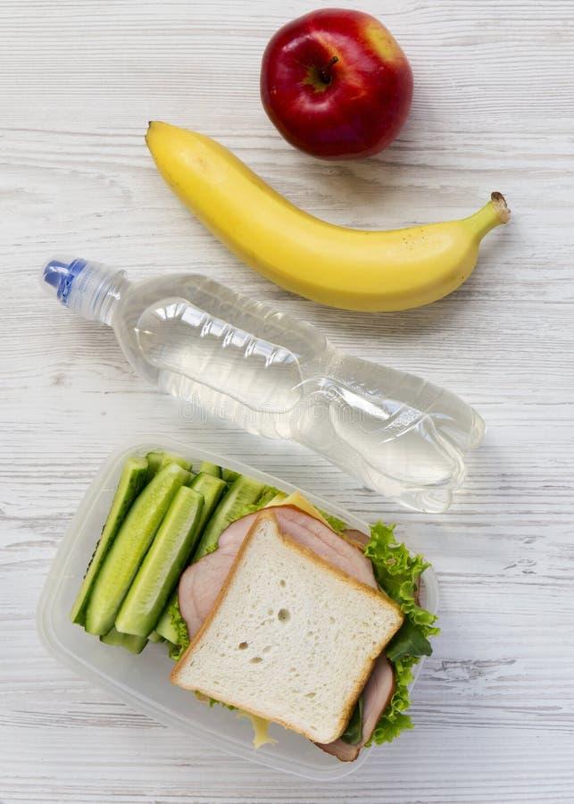 Caixa de almoço escolar saudável com sanduíche, frutos e garrafa da água na superfície de madeira branca, configuração lisa De ci imagens de stock