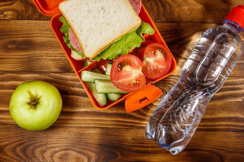 Caixa de almo?o escolar com sandu?che e legumes frescos, garrafa da ?gua e ma?? verde na tabela de madeira imagens de stock royalty free