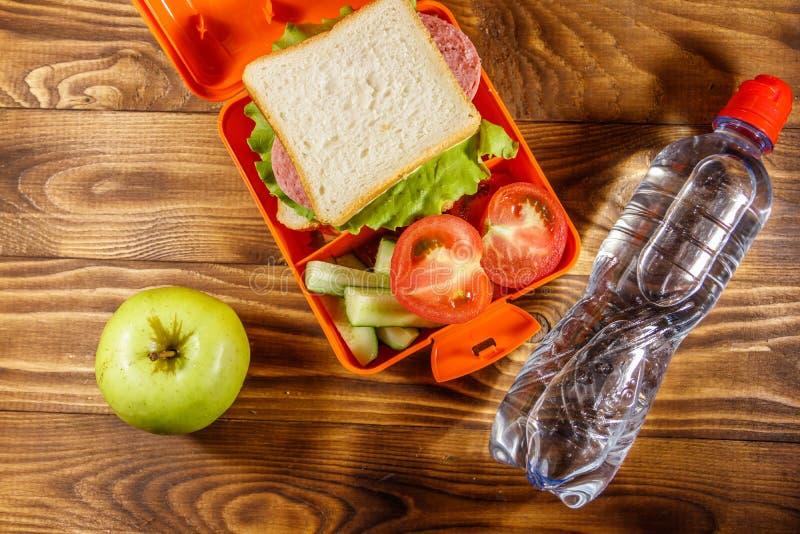 Caixa de almo?o escolar com sandu?che e legumes frescos, garrafa da ?gua e ma?? verde na tabela de madeira fotos de stock royalty free
