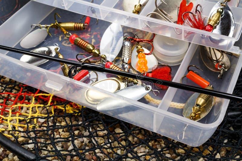 Caixa de armazenamento aberto com os acessórios para pescar e as iscas de pesca na terra rochoso fotografia de stock