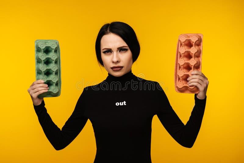 Caixa de cartão da posse do retrato da mulher isolada no fundo amarelo fotografia de stock royalty free