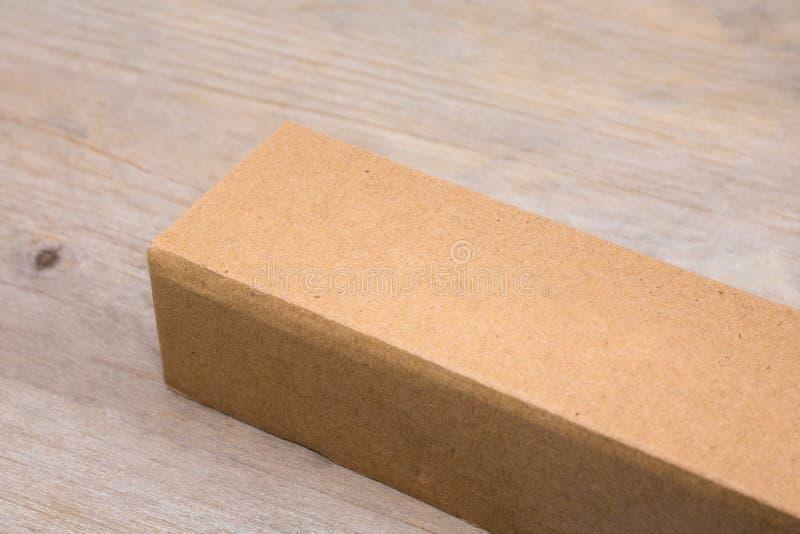 Caixa de cartão no fundo de madeira da tabela Molde da caixa longa para seu projeto Empacotamento reciclado do produto imagens de stock