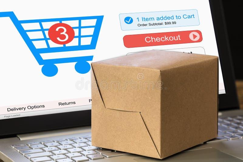 Caixa de cartão no portátil com o carrinho de compras indicado na tela fotos de stock
