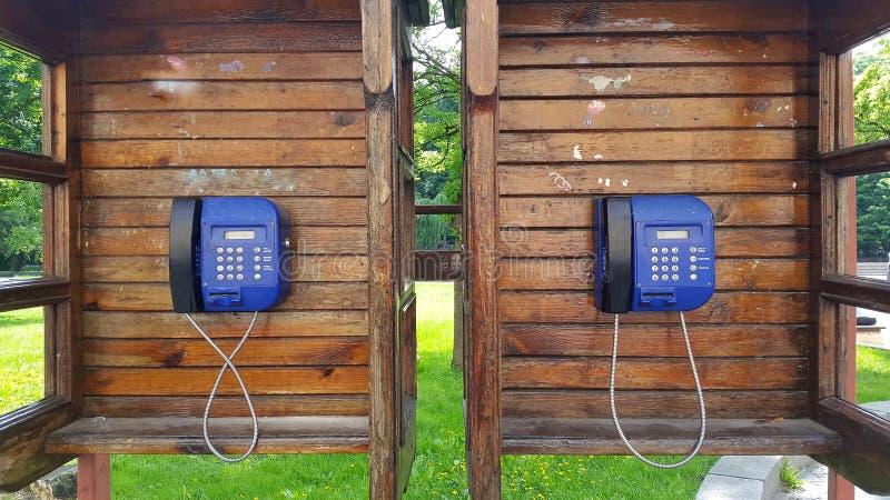 caixa de chamada dois de madeira com telefone azul imagens de stock royalty free