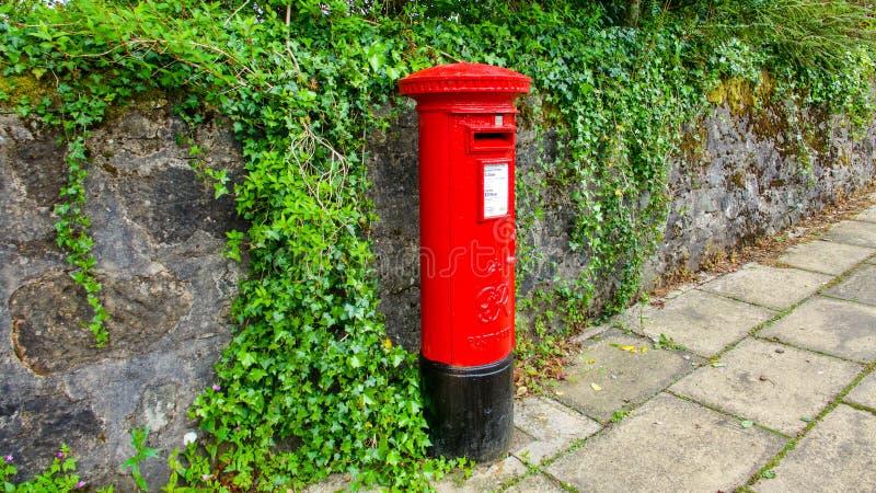 Caixa de coluna vermelha da estação de correios na frente da parede de pedra coberta na hera imagens de stock royalty free