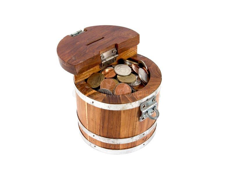 Caixa de dinheiro de madeira redonda com o fechamento completo com as moedas isoladas no fundo branco imagem de stock royalty free