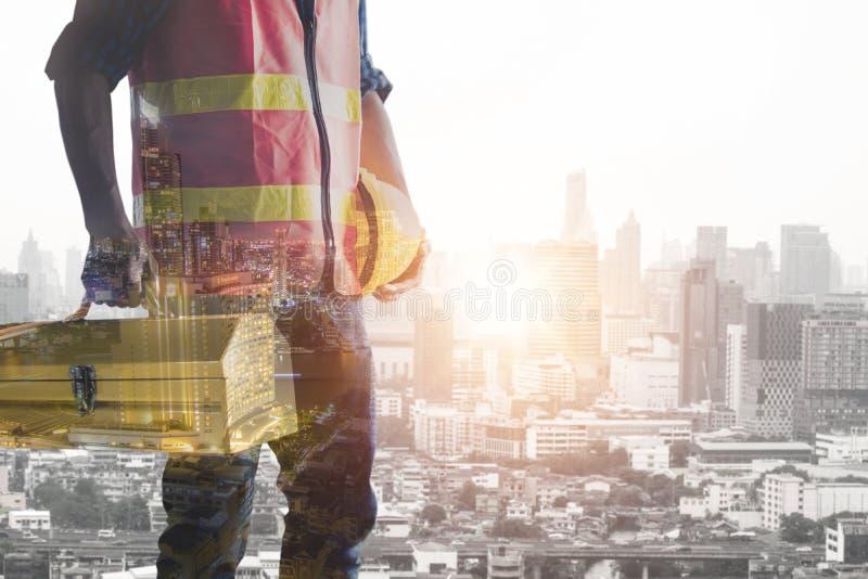 Caixa de ferramentas da terra arrendada do trabalhador da construção com fundo da cidade imagens de stock royalty free