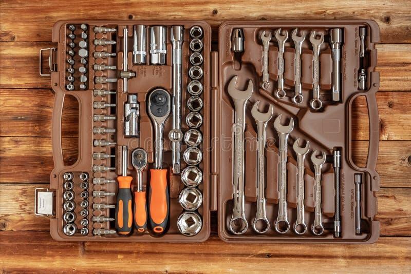 Caixa de ferramentas, grupo de chaves e bocados no fundo de madeira marrom Jogo de ferramentas Vista superior fotos de stock