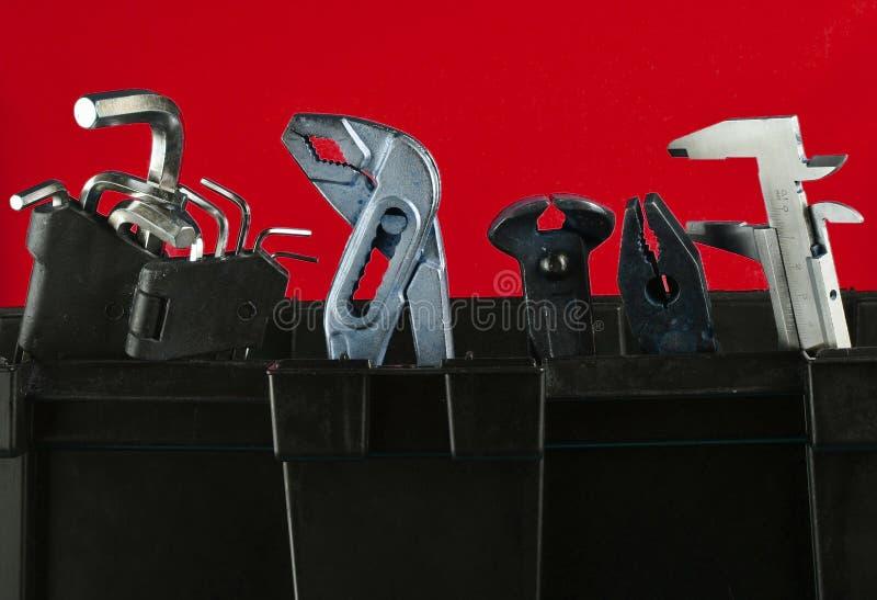 Caixa de ferramentas plástica da garagem com as ferramentas de funcionamento isoladas no azul fotos de stock royalty free