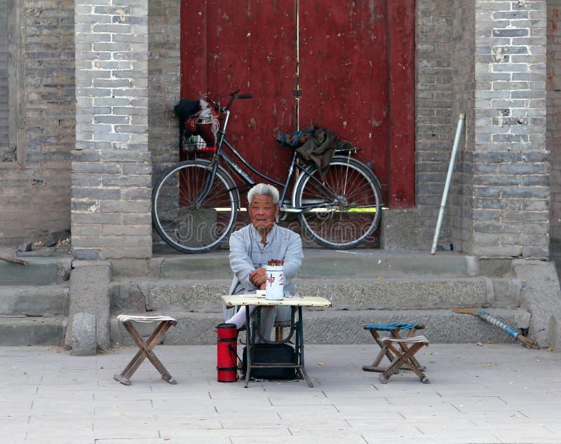 Caixa de fortuna chinês que senta-se na entrada a um monastério budista imagens de stock royalty free