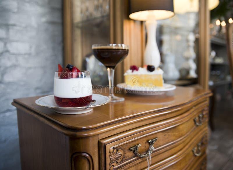 Caixa de gavetas antiga, de sobremesa do panakota, de sobremesa do chocolate e de um pedaço de bolo fotografia de stock royalty free