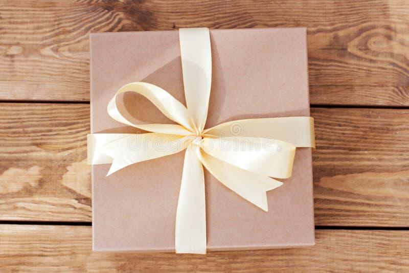 Caixa de Kraft para os presentes amarrados com uma curva em placas de madeira fotos de stock