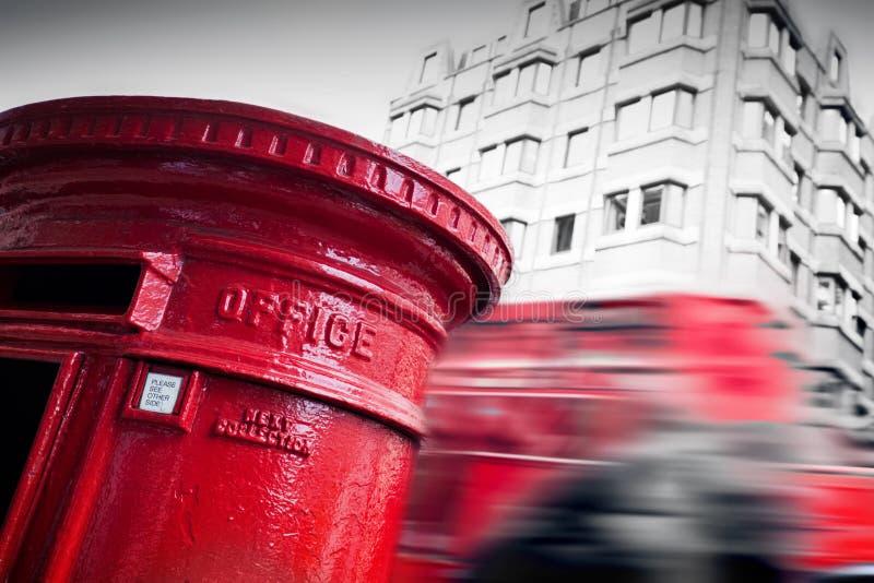 Caixa de letra vermelha tradicional do correio e ônibus vermelho no movimento em Londres, o Reino Unido imagem de stock