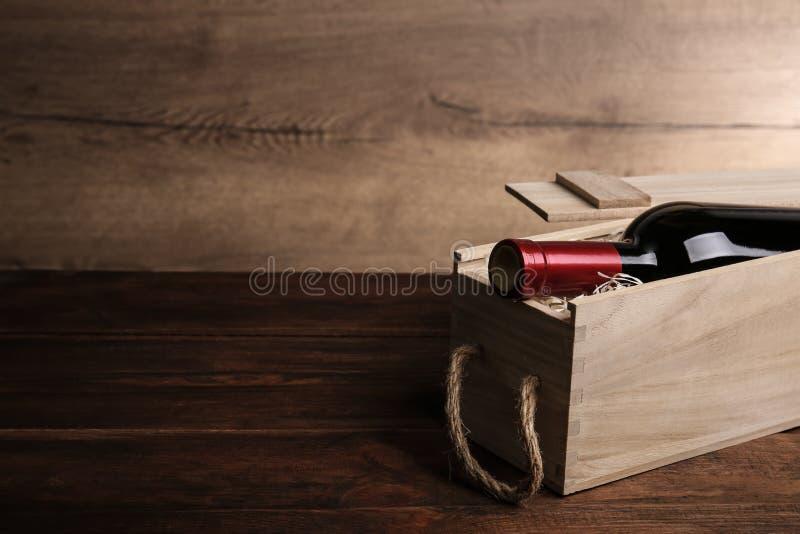 Caixa de madeira aberta com a garrafa do vinho na tabela, espaço para foto de stock