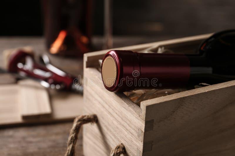 Caixa de madeira aberta com a garrafa do vinho no borrado imagem de stock royalty free