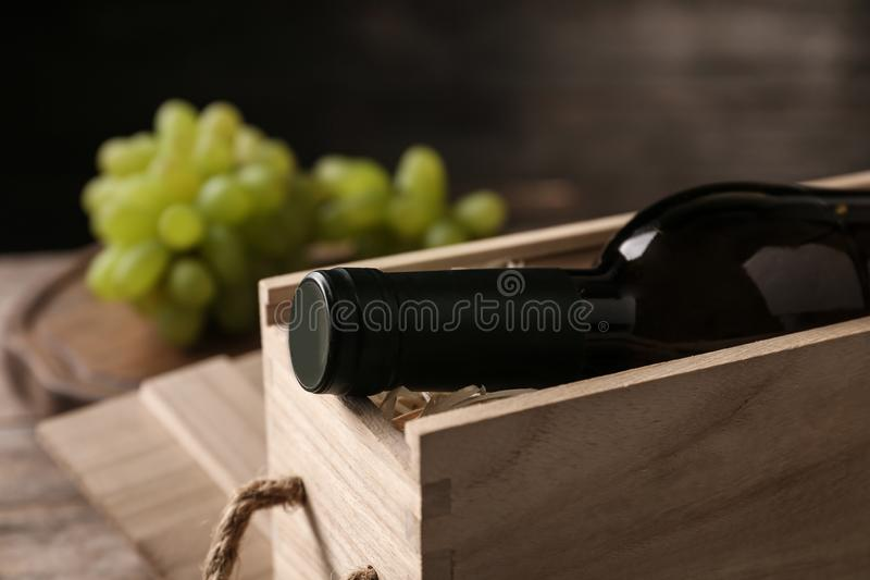 Caixa de madeira aberta com a garrafa do vinho no borrado imagem de stock