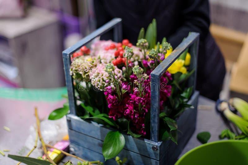 Caixa de madeira bonita das flores do carmesim, as brancas e as amarelas decoradas com folhas verdes fotos de stock royalty free