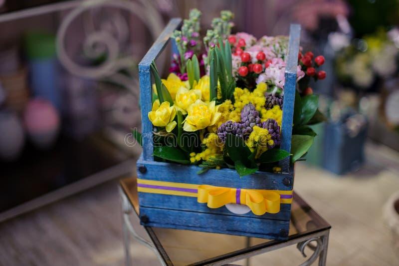 Caixa de madeira bonita das flores do carmesim, as brancas e as amarelas decoradas com folhas verdes e as bagas vermelhas fotos de stock