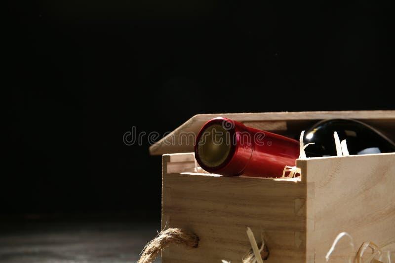 Caixa de madeira com a garrafa do vinho no fundo escuro, close up Espa?o para imagem de stock