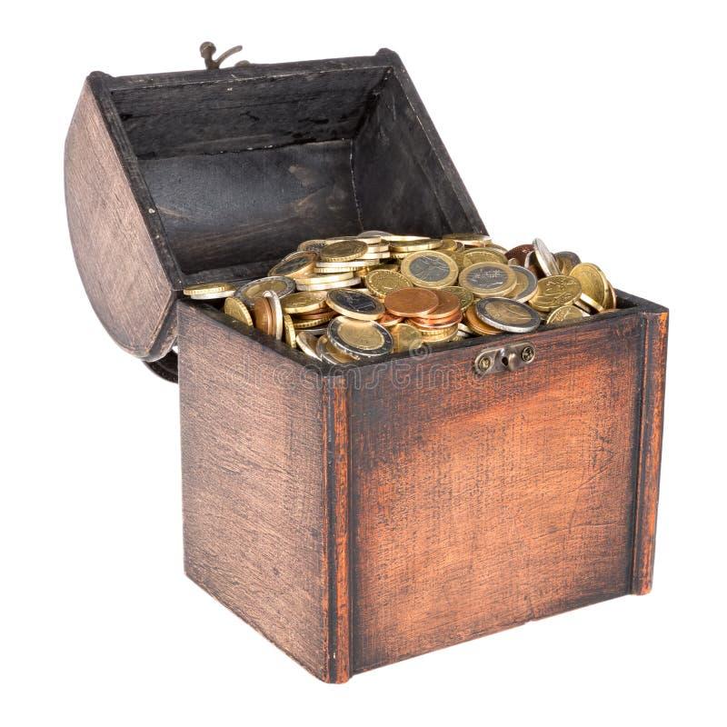 A caixa de madeira do dinheiro encheu-se com as moedas isoladas sobre o branco imagens de stock