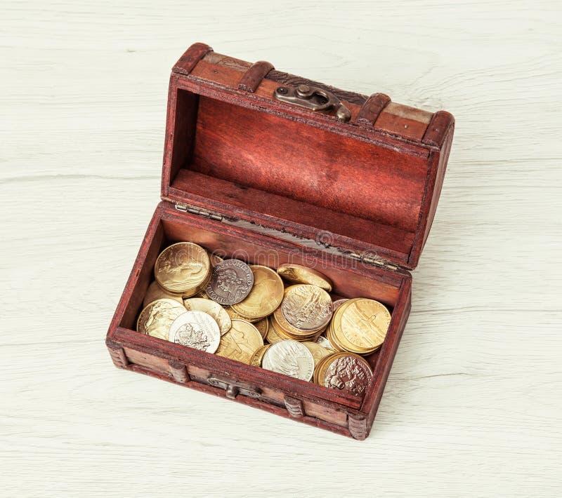 Caixa de madeira do dinheiro enchida com as moedas imagem de stock royalty free