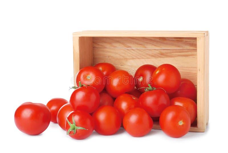 Caixa de madeira virada com os tomates maduros frescos fotografia de stock royalty free