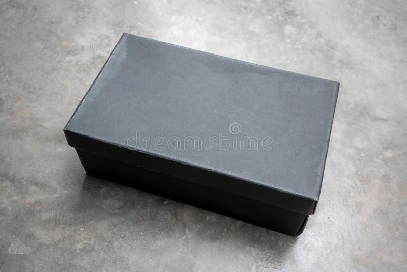 Caixa de papel preta do retângulo no assoalho concreto foto de stock royalty free