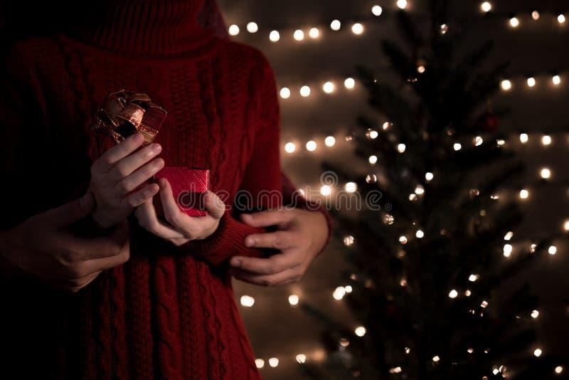 Caixa de presente aberta dos pares felizes no fundo das luzes do bokeh do Natal no feriado de inverno fotos de stock royalty free