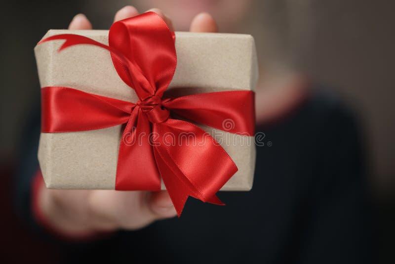 Caixa de presente adolescente fêmea do papel do ofício da mostra da mão com curva vermelha foto de stock royalty free
