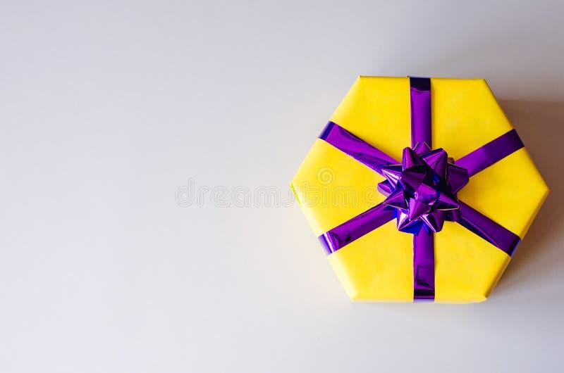 Caixa de presente amarela com uma curva roxa imagem de stock