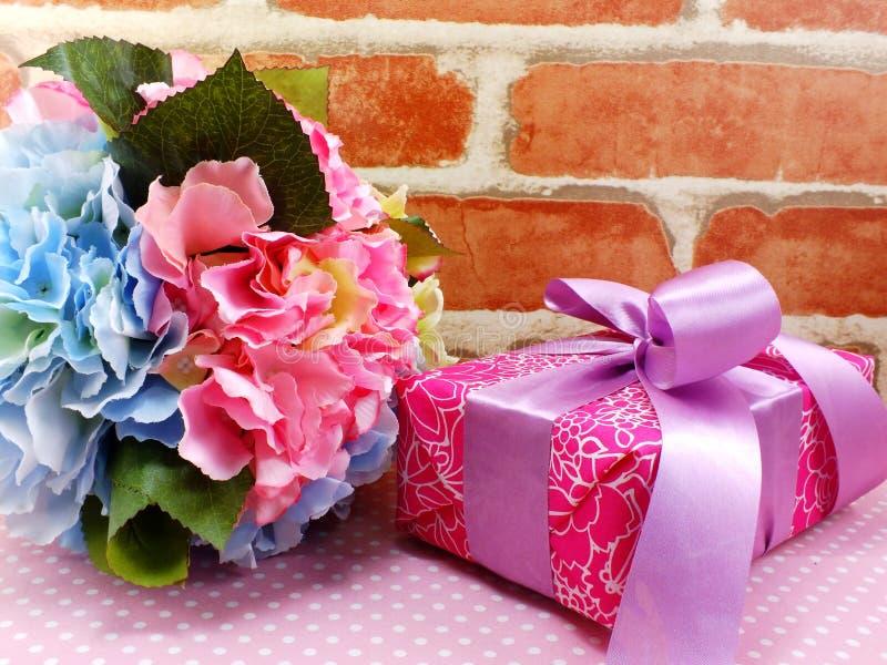 Caixa de presente atual com curva cor-de-rosa da fita e fundo bonito das flores fotos de stock