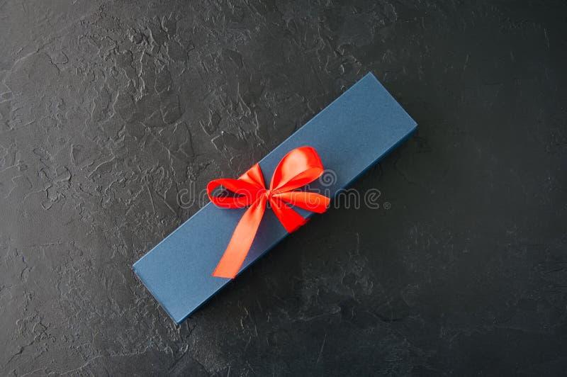 Caixa de presente azul com a burocracia com chocolate em uma parte traseira preta da pedra fotografia de stock