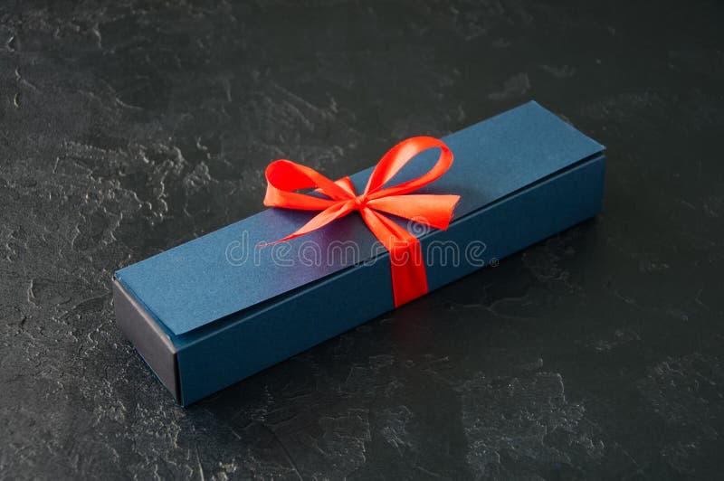 Caixa de presente azul com a burocracia com chocolate em uma parte traseira preta da pedra imagem de stock