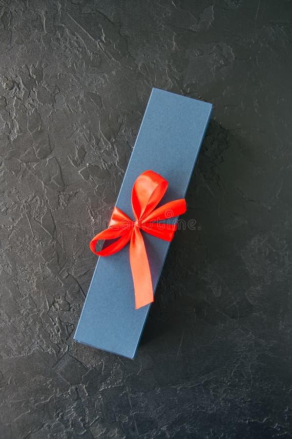 Caixa de presente azul com burocracia e chocolate em um backg de pedra preto imagem de stock royalty free