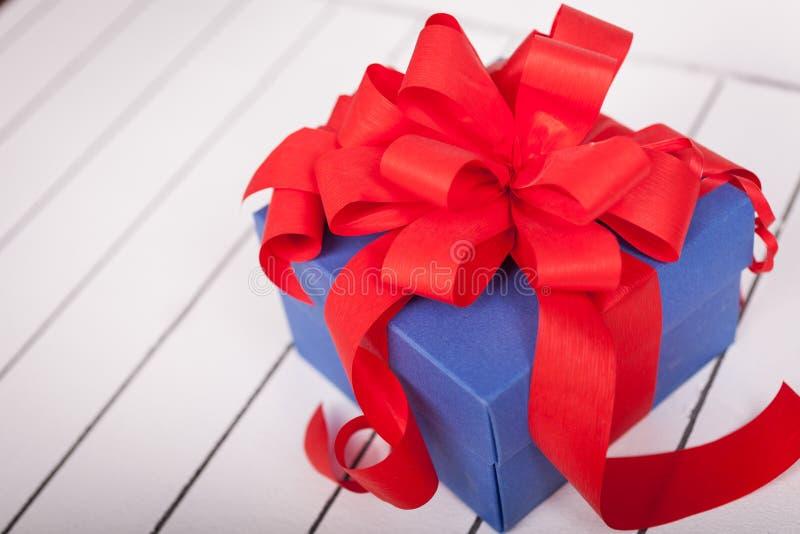 Caixa de presente azul com fita vermelha e curva no fundo de madeira fotos de stock royalty free
