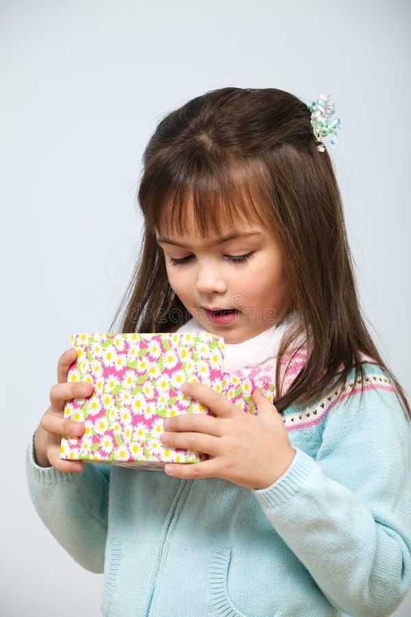 Caixa de presente bonito da abertura da menina fotografia de stock royalty free