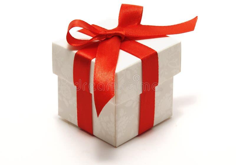 Caixa de presente branca com curva vermelha da fita do cetim fotografia de stock