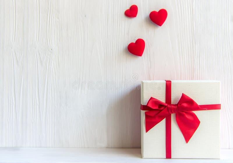 Caixa de presente branca do dia de Valentim com uma curva vermelha no fundo branco da parede, fotos de stock royalty free
