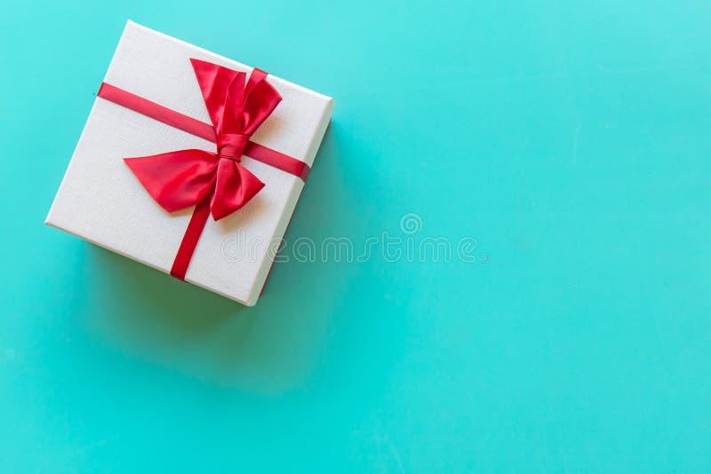 Caixa de presente branca do dia de Valentine's com uma curva vermelha no fundo completo da parede da cor, espaço da cópia imagem de stock