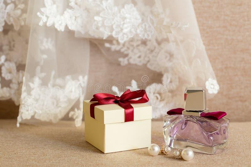 Caixa de presente, brincos, perfume, e o véu da noiva imagem de stock