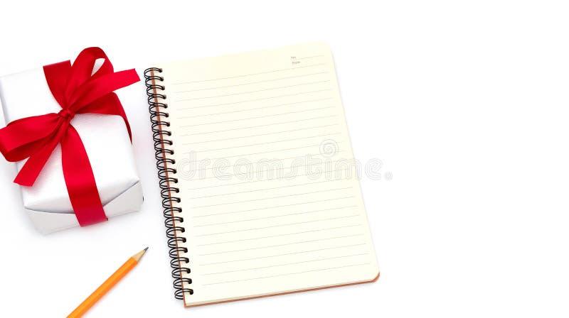 Caixa de presente com bloco de notas, amarelo do lápis colocado na mesa isolada no fundo branco imagens de stock royalty free