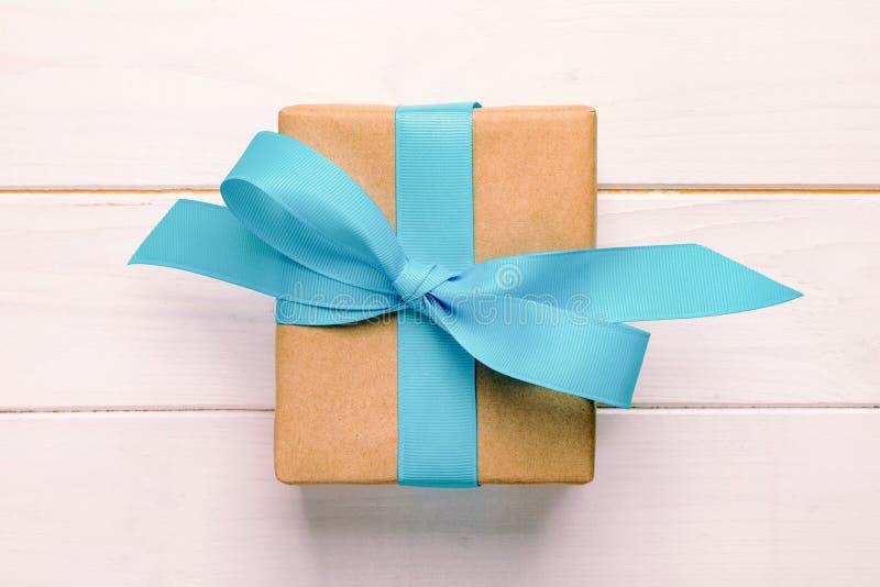 Caixa de presente com curva azul sobre a tabela de madeira branca com espaço da cópia vintage, vista superior tonificada imagens de stock royalty free
