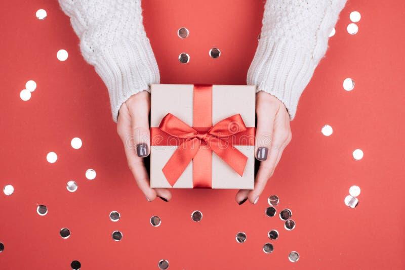 Caixa de presente com curva nas mãos da mulher imagem de stock royalty free