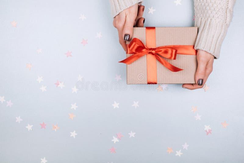 Caixa de presente com curva nas mãos da mulher fotografia de stock