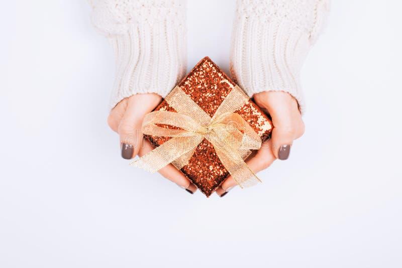 Caixa de presente com curva nas mãos da mulher foto de stock