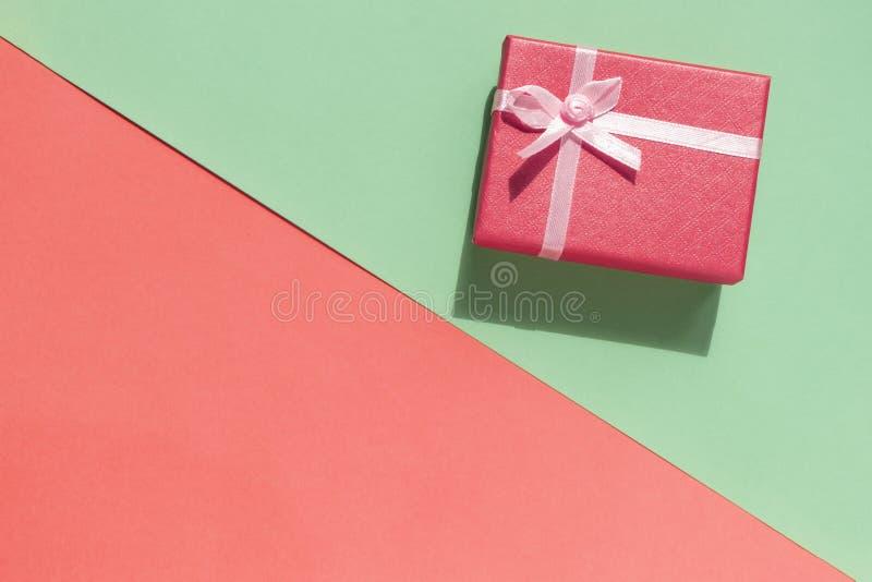 Caixa de presente com curva no rosa e no fundo verde Vista superior fotos de stock